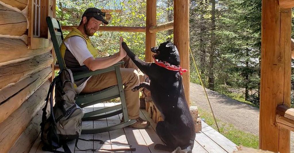man sitting on porch with black dog wearing red bandana