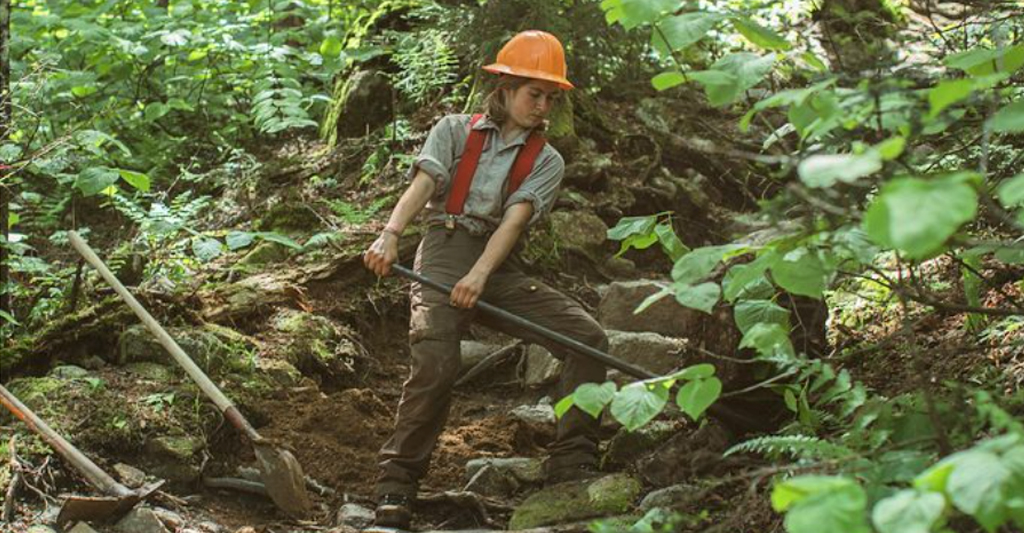 Young woman restoring rocky trail on the incline side of a mountain.