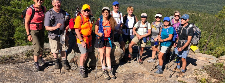 group of hikers atop a rocky hill, smiling, wearing warm weather gear