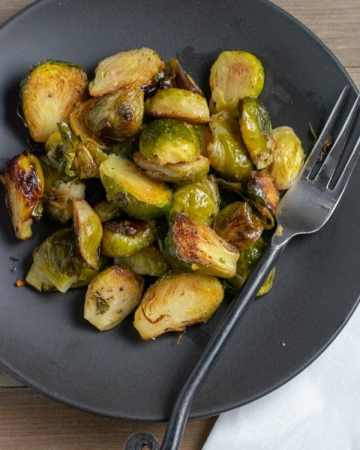 baked brussels sprouts on black plate with fork