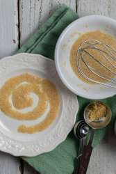 Flax egg used to paint a spiral on a white plate