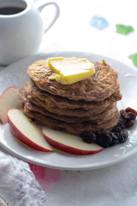 Flourless Oatmeal Pancakes with ghee and fruit on white plate