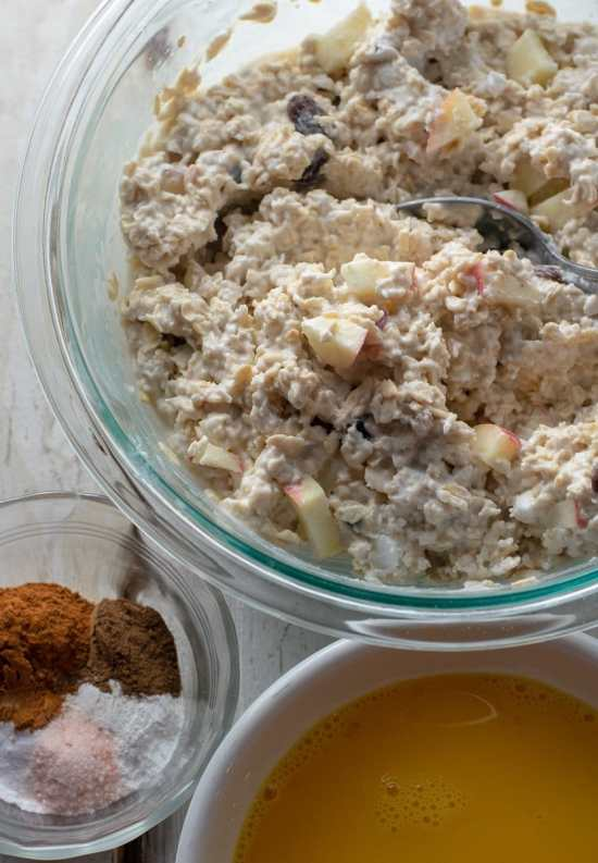 Oats, raisins and apples in coconut milk with eggs and spices in bowls