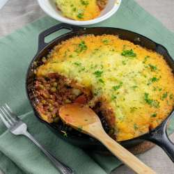 Beef Shepherd's Pie in iron pan partly served on white plate