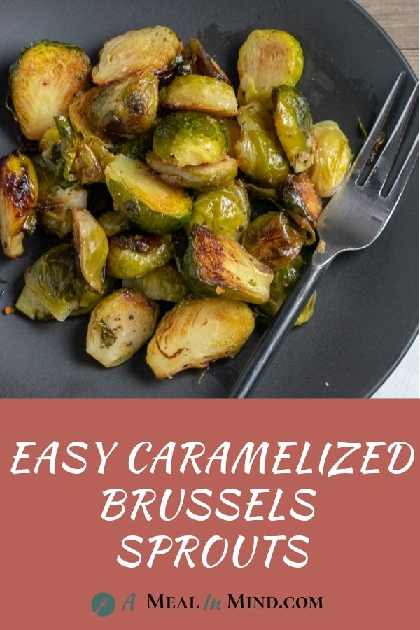 roasted brussels sprouts with fork on black plate
