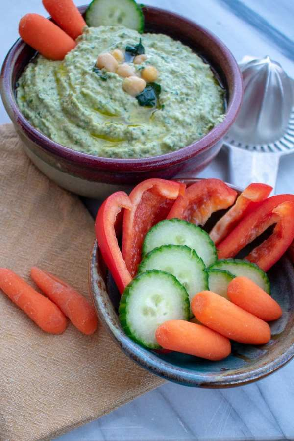 Garlicky spinach artichoke hummus in red bowl from side