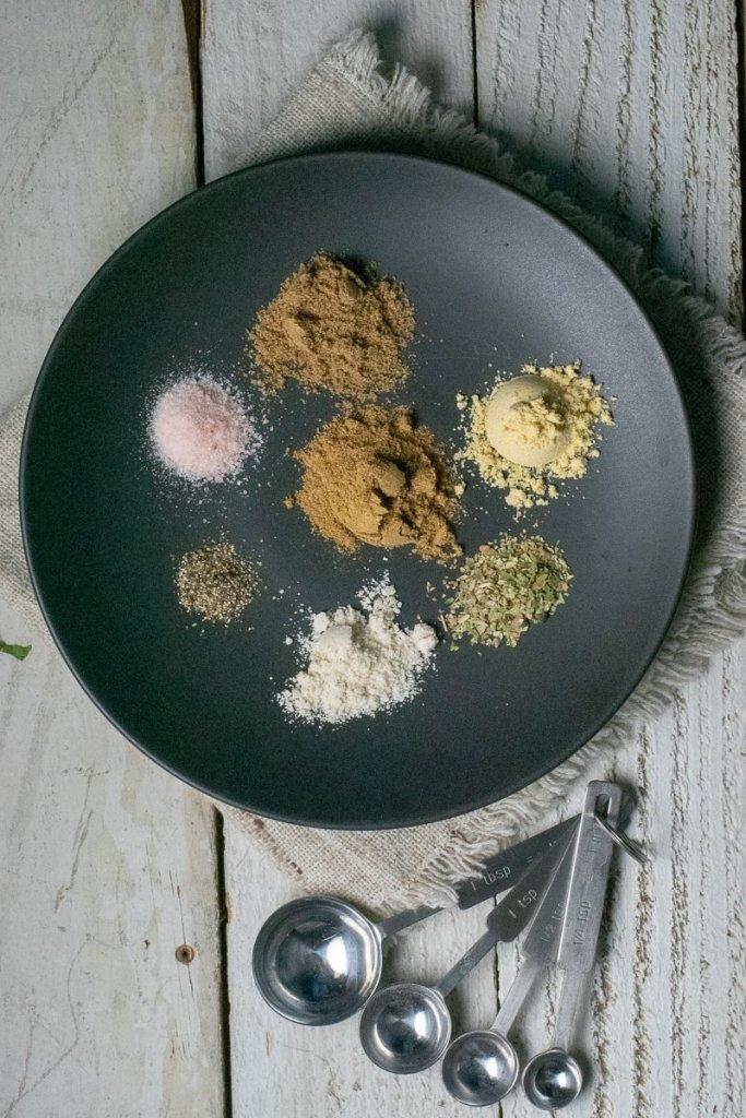 Taco seasoning ingredients on black plate with measuring spoons