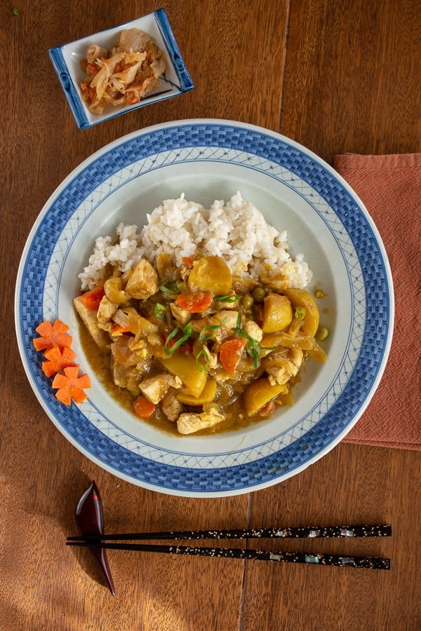 Japanese chicken curry on rice on a blue plate with chopsticks and condiment dish