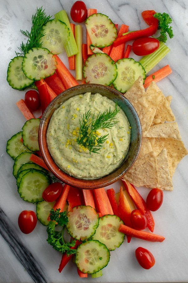 white bean lemon dill dip with vegetable dippers overhead view