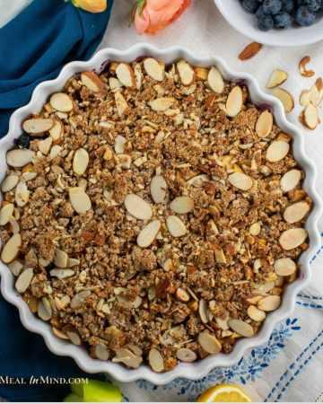 blueberry apple crisp in white tart pan on tablecloth