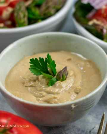 tahini garlic dressing in white bowl with salads in the background