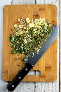 chopping garlic, fennel and rosemary on bamboo board