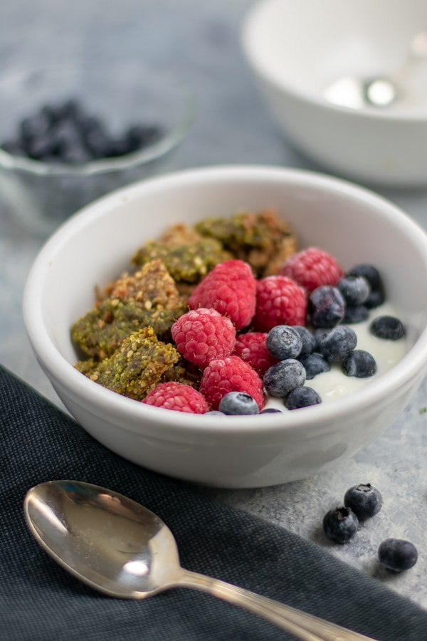 moringa fruit-nut-ola in white bowl with berries side view