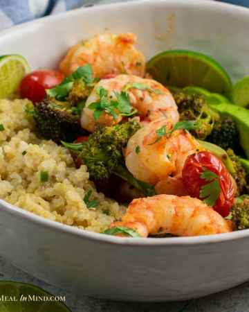 close up of roasted shrimp with broccoli and tomatoes in bowl with quinoa and avocado