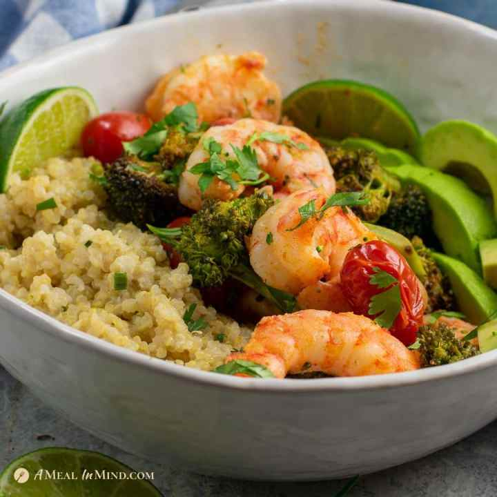 roasted shrimp with broccoli and tomato bowl with coconut milk quinoa in white bowl