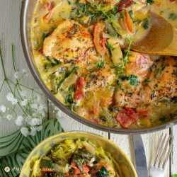 tuscan chicken with spinach, tomatoes, and artichokes in steel pan