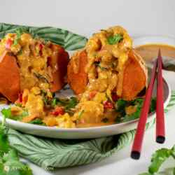square image of thai massaman curry stuffed sweet potato on white plate