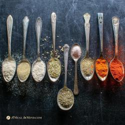 individual herbs and spices for cajun seasonings in small silver spoons