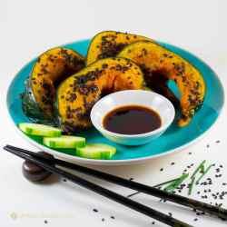 roasted kabocha with black sesame on blue plate