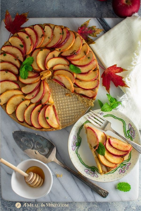 apple-marzipan tart with almond crust with one slice served