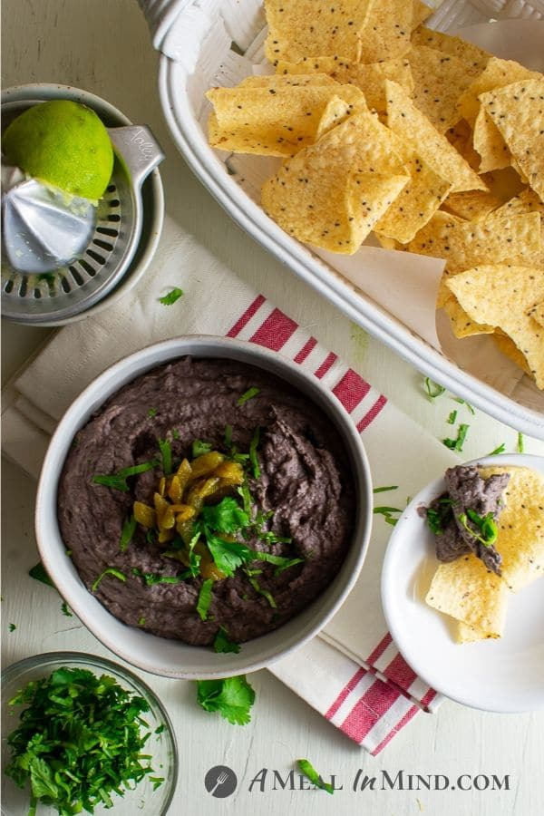cheese green chile black bean dip in white bowl with corn chips