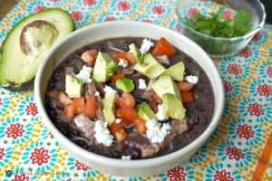 Green chile chicken enchilada soup in white bowl with toppings