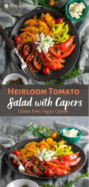 pinterest image of heirloom tomato salad with capers and feta on black plate