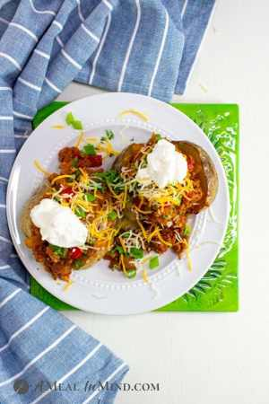 Sloppy Joe Stuffed Potatoes overhead view on white plate with garnishes