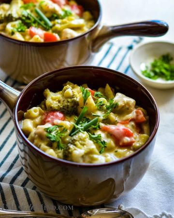 Creamy Mac and Cheese Chicken Soup in soup bowls with spoons side view