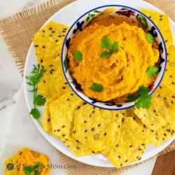 Moroccan Roasted-Carrot Hummus on white plate with multigrain chips