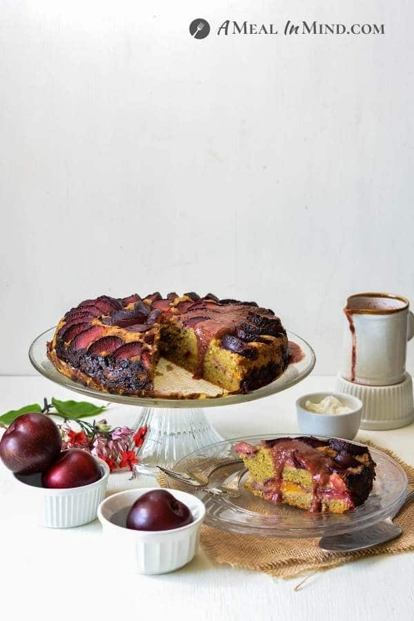delicious Plum Breakfast Cake with Plum Sauce on glass cake platter with plums