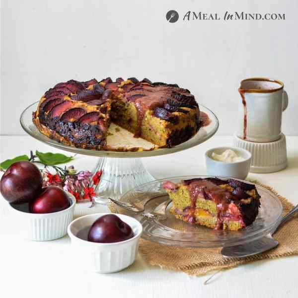 Plum Breakfast Cake with Plum Sauce on glass platform and plates with plums