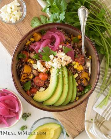 mexican quinoa bowl in brown bowl with toppings