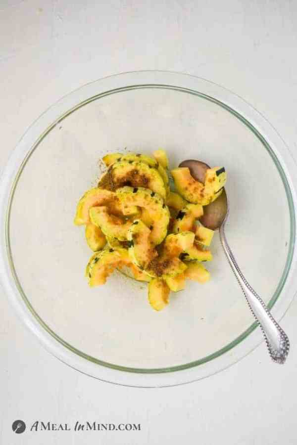 cut delicata squash pieces in glass bowl with spoon