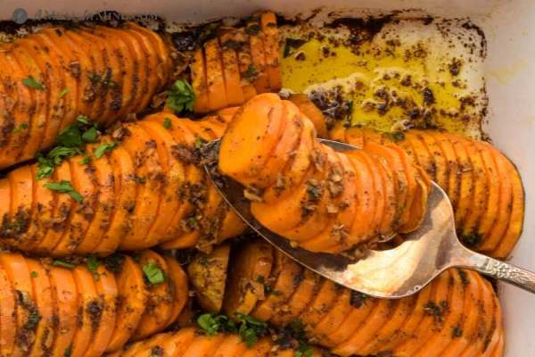 roasted sweet potatoes being served from white baking dish
