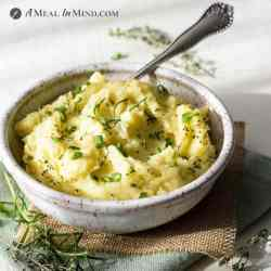 garlic mashed potatoes in speckled bowl