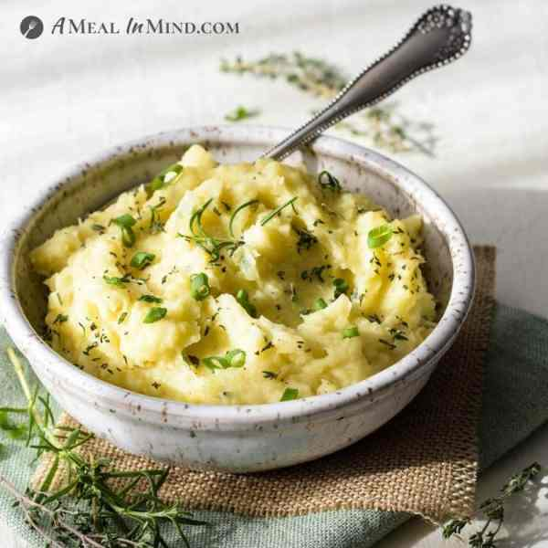 garlic mashed potatoes in speckled bowl with spoon