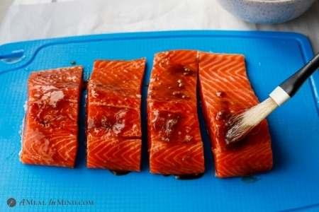brushing hoisin sauce mixture onto salmon fillets