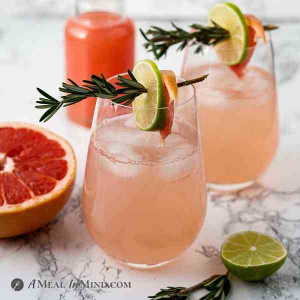 paloma mocktails with organic sugar in two tall glasses with rosemary garnishes