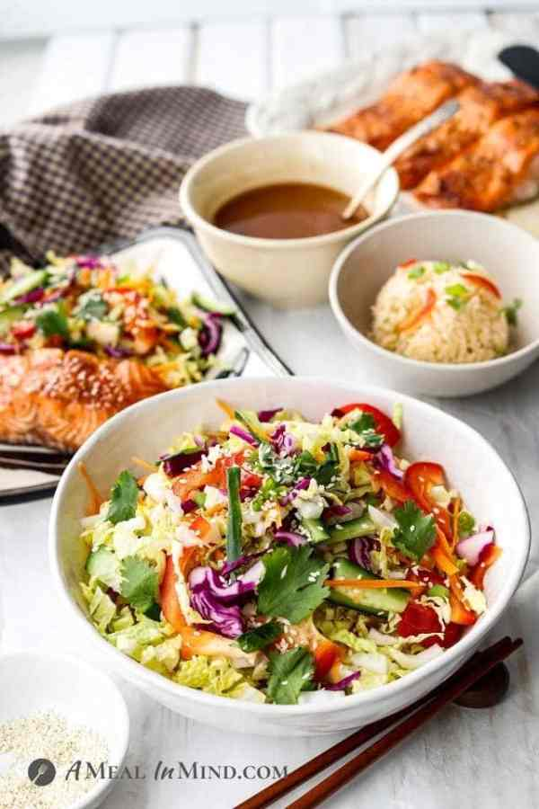 bowl of asian slaw in foreground with hoisin salmon and rice