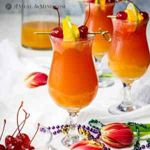 three hurricane mocktails in glasses on white cloth
