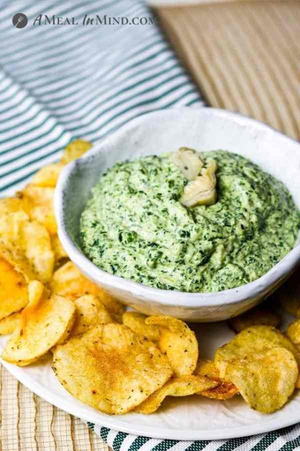 side view of spinach-artichoke dip in white bowl