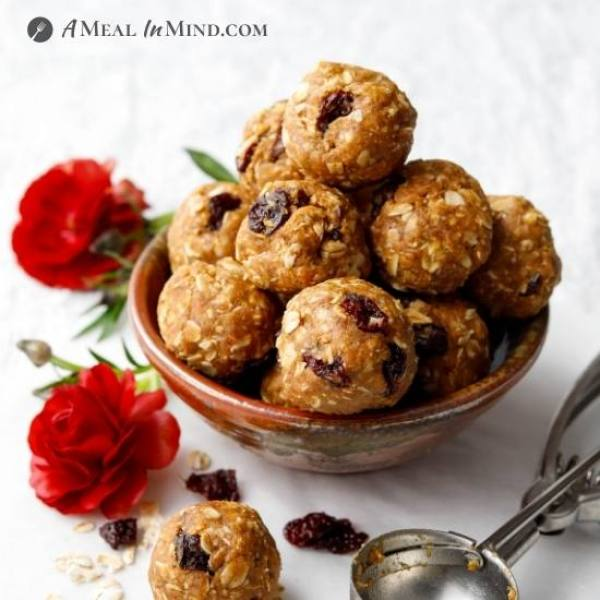 cherry almond-oat bites in small bowl with red flowers