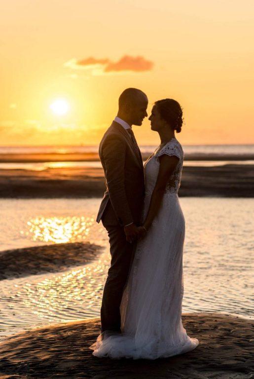 Bruidspaar bij zonsondergang op het strand van Ameland