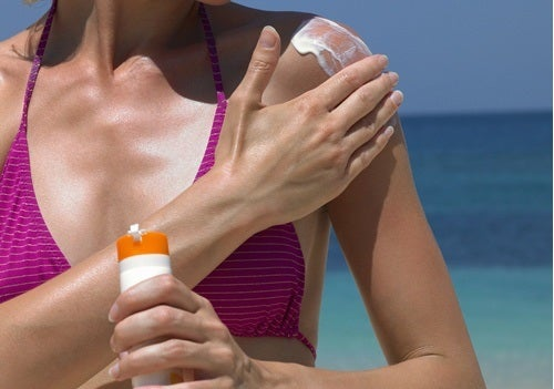 Woman at the beach putting sunscreen