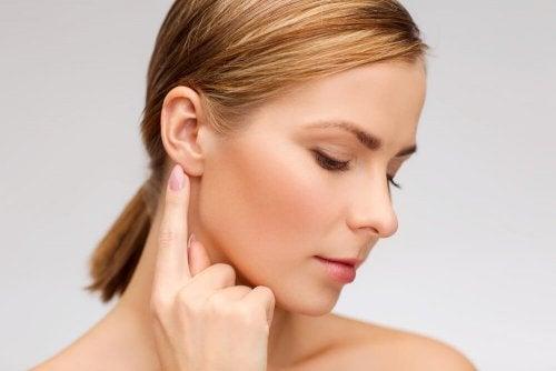 Femme qui pointe du doigt son oreille