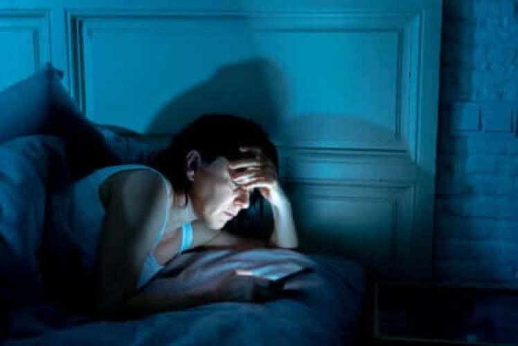 Une femme qui regarde une tablette dans son lit la nuit.