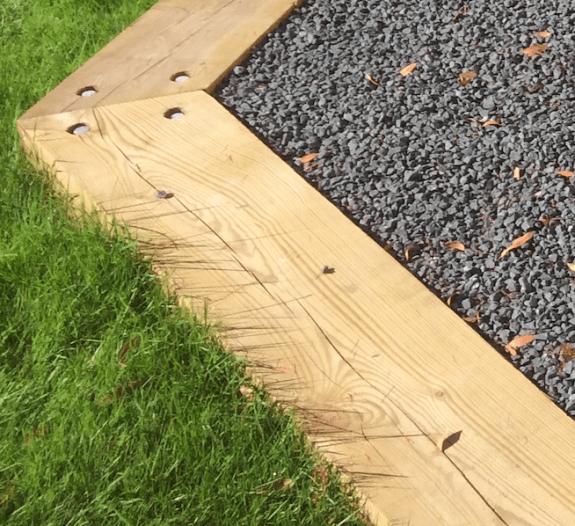 bordure avec une poutre de bois pour délimiter le gazon de l'allée gravillon dans le jardin
