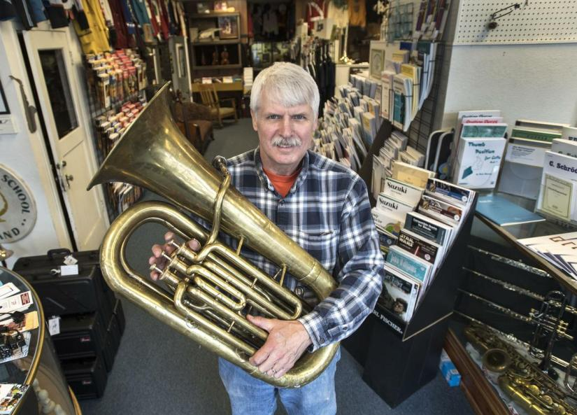 "Robin Amend, of Amend Music Center, with a 1950s-era tuba. Instrument repair requires one to be a perfectionist, he said, ""particularly if you're working with professional musicians' instruments."" (Dan Pelle / The Spokesman-Review)"