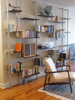 A custom midcentury modern bookcase separates the living room from the dining room and creates display for collectibles.